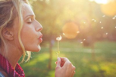 women blowing dandelion